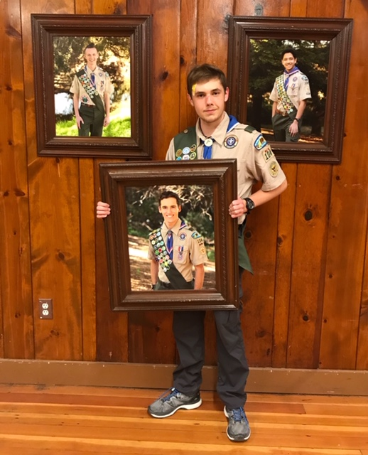Alex Kondracki with portraits of fellow Eagle Scouts.
